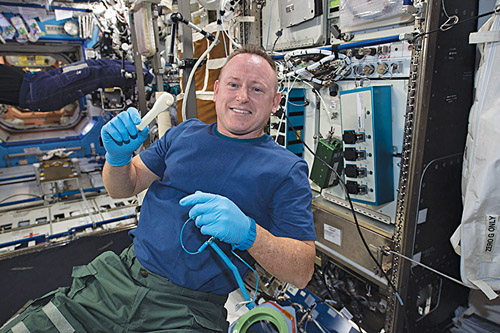 """International Space Station Expedition 42 commander Barry """"Butch"""" Wilmore shows off a ratchet wrench made with a 3D printer on the station. It took about four hours for the printer to make the wrench, thereby allowing astronauts to reliably print what was required and not depend on carrying supplies from the Earth (Image courtesy: www.nasa.gov)"""