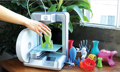 Fig. 6: A home 3D Printer and its colourful toy printouts (Source: www.3dsystems.com)