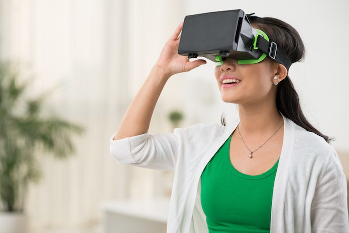 Woman in virtual reality glasses playing the game