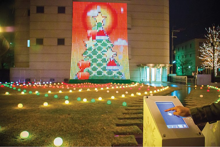 """""""Touch the Lights!"""" Last year, over Christmas, ROHM held Touch the Lights, a participatory-style event. At the event, every time a person ran a fingertip along an installed touch display, trees and cakes on the big screen would be decorated along with it"""