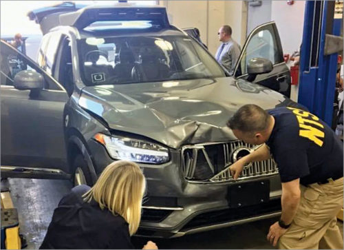 National Transportation Safety Board investigators examine Uber's self-driving vehicle that was involved in a fatal accident in Tempe, Arizona, in March 2018