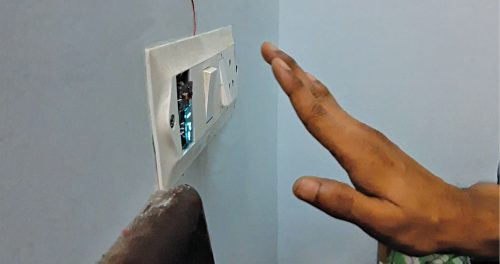 Moving hand up in front of the contactless switch switches on light bulb
