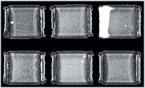 Part of a tray of MLCCs; white features are defects